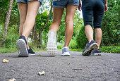 トレイルを歩く3つのハイキング女の子の足