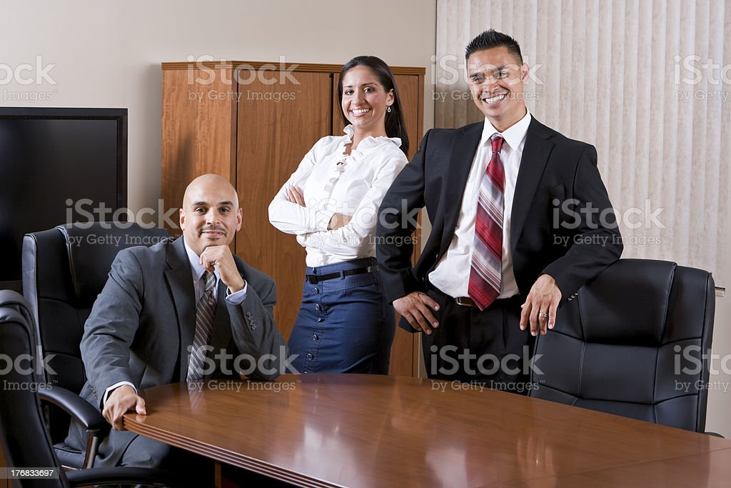 Three Hispanic office workers in boardroom royalty-free stock photo