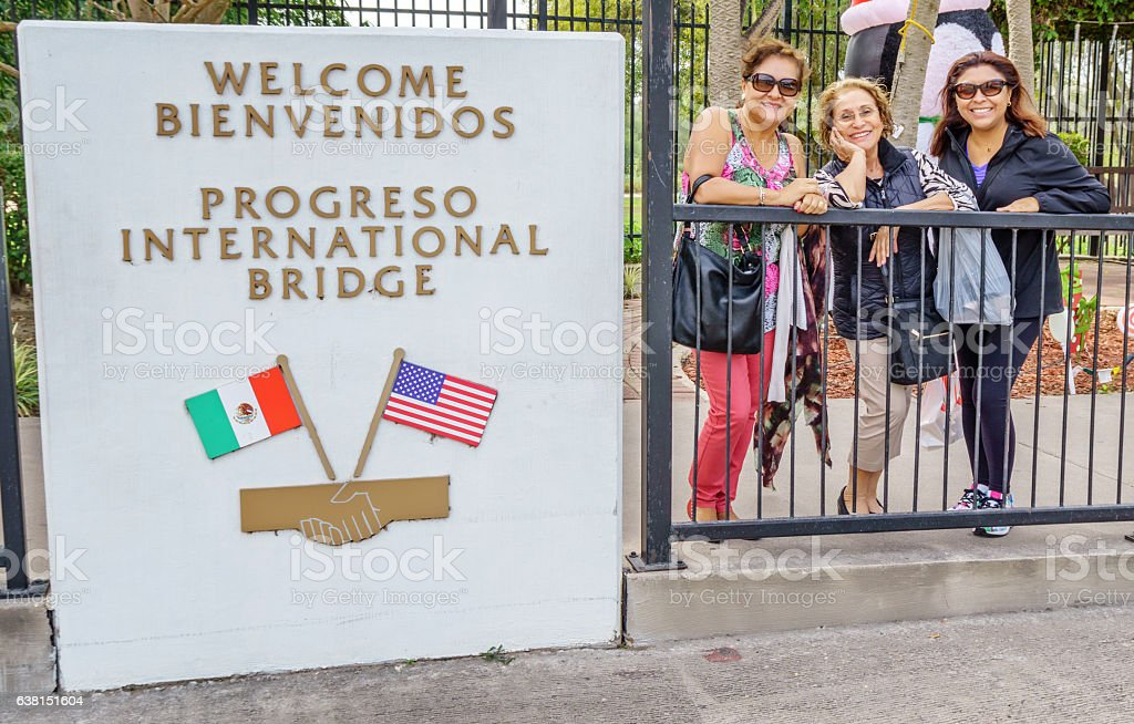Three hispanic women on bridge between USA and Mexico stock photo