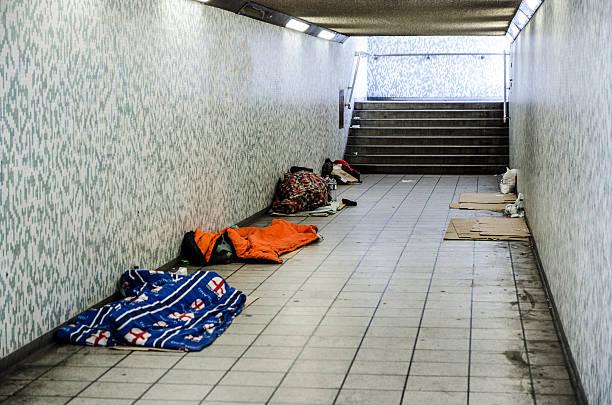 Three homeless people sleeping in sleeping bag in a tunnel