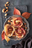 Three homemade puff pastries with rose shaped apple slices on metal plate. Top lay on wooden board with Autumn leaves and caramelized nuts.