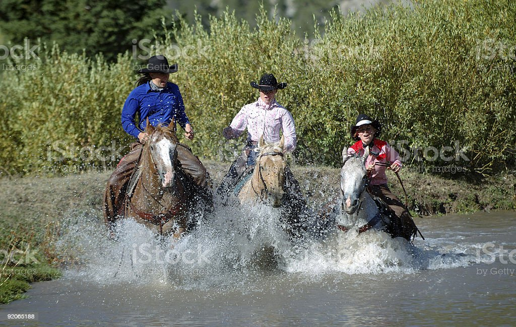 Three Horses & Riders Splashing Through Pond stock photo