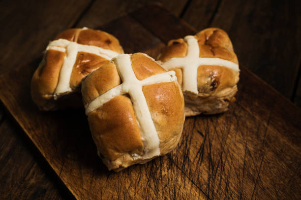 Three Hot cross buns on an aged wood surface. stock photo