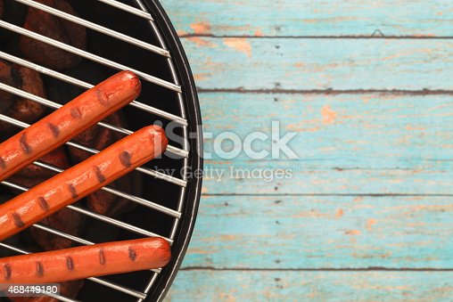 470765518 istock photo Three Hotdogs Grilling on Rustic Blue Picnic Table 468449180