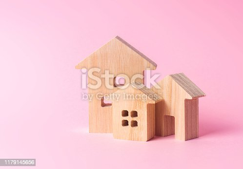 istock Three houses on a pink background. Buying and selling of real estate, construction. Apartments and residential buildings in a city or settlement. Investments. mortgage loan. Housing Maintenance 1179145656