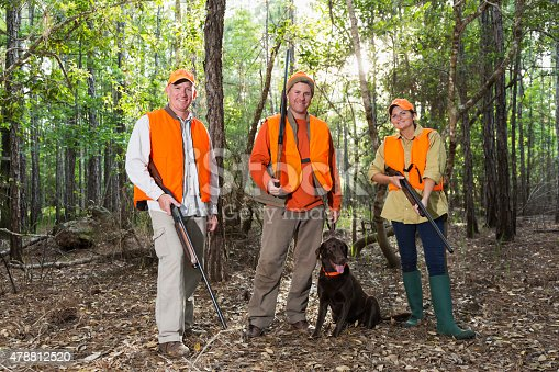 A group of three hunters, a woman and two men, with a hunting dog, a brown labrador retriever, standing in the woods, wearing orange safety vests and hats, smiling at the camera.  They are hunting game with shotguns.