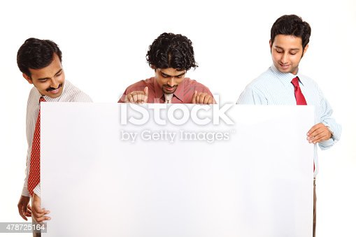 istock three Indian businesspeople holding the white board 478725164