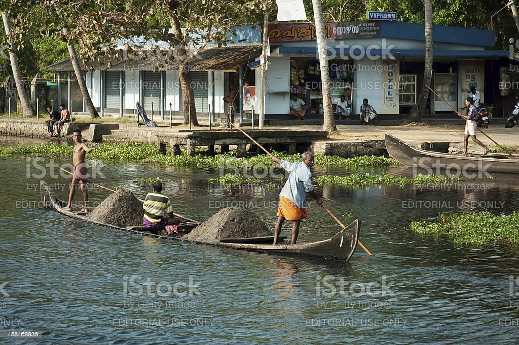 Three indian men transporting soil in the boat stock photo