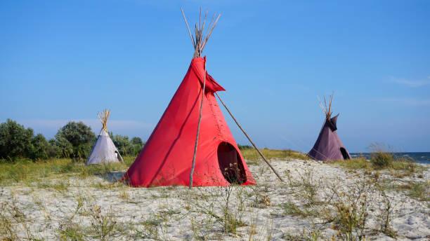 drei indische wigwams lodge oder tipi an der küste im sommer. - weidentipi stock-fotos und bilder