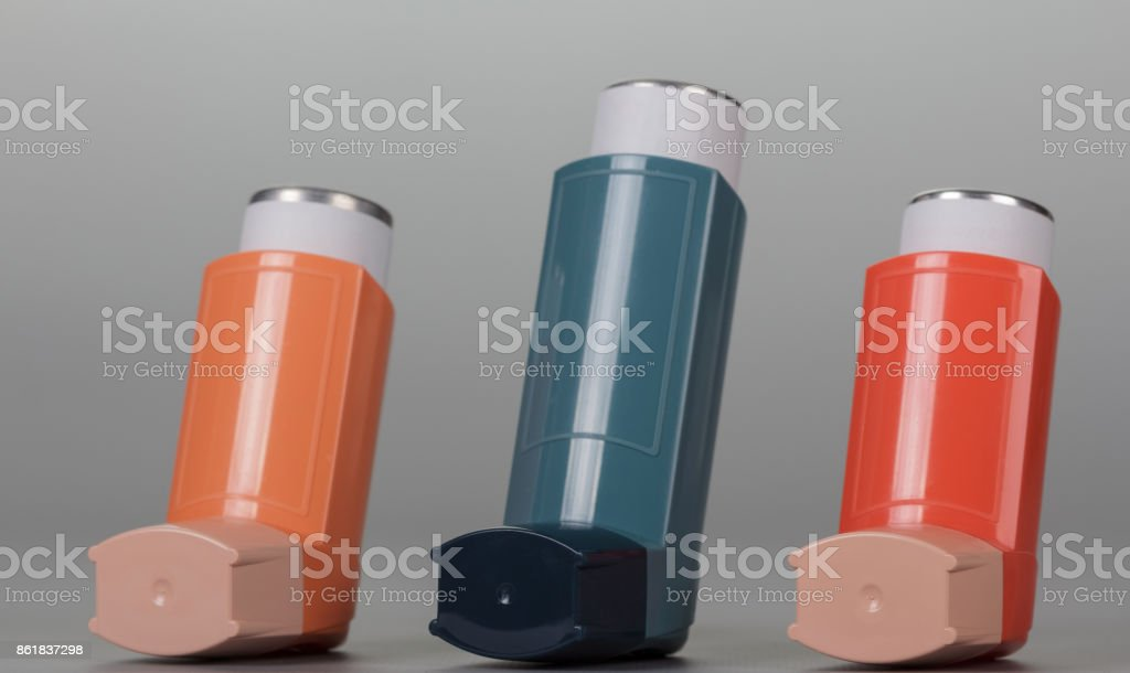 Three inhaler aerosol on grey background. stock photo
