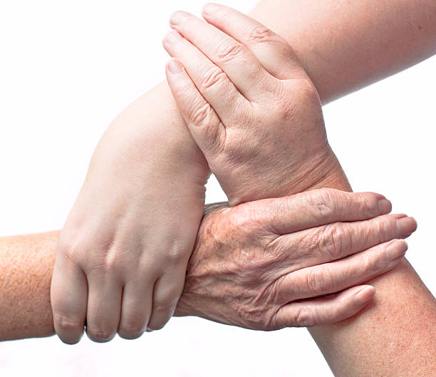 Three Interlocked Female Hands Of Different Ages stock photo