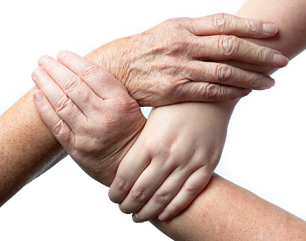 Three Interlocked Hands Of Different Ages stock photo
