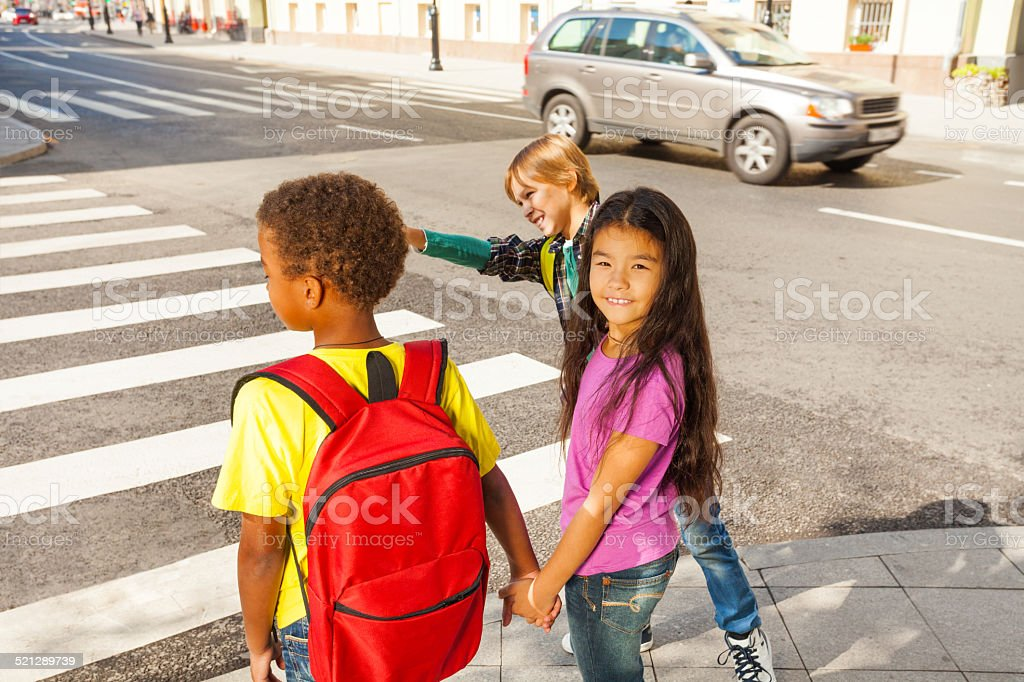 Three international kids ready to cross road stock photo