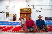 Semporna, Malaysia - Nov 14, 2009: Three islamic Malaysians sitting on the floor in a mosque in Semporna, the west Malaysia.