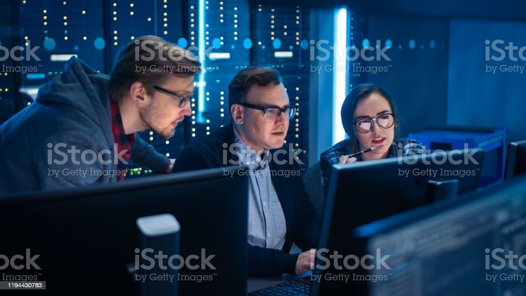 Three IT Engineers / Programmers Talking about Work, Using Computers. Technical Department with Data Server Racks. Software Development / Code Writing / Website Design / Database Architecture - Royalty-free Adult Stock Photo