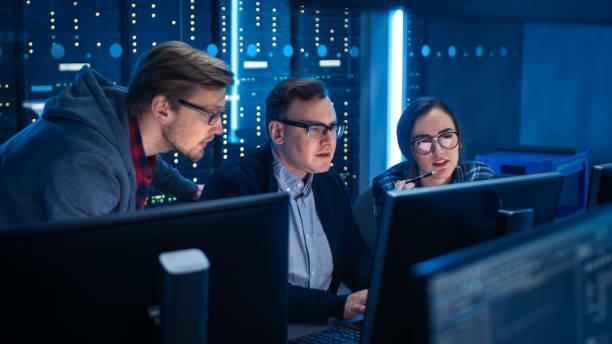 Drei IT-Ingenieure / Programmierer sprechen über Arbeit, Computernutzung. Technische Abteilung mit Data Server-Racks. Softwareentwicklung / Code-Schreiben / Website-Design / Datenbankarchitektur – Foto