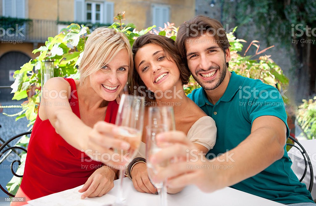 Three Italian friends toasting with you in an outdoor restaurant. stock photo