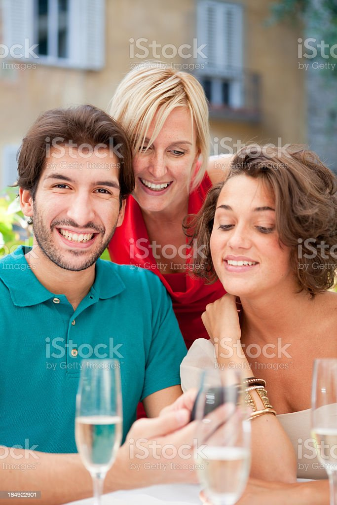Three Italian friends with a smart phone in outdoor restaurant. stock photo