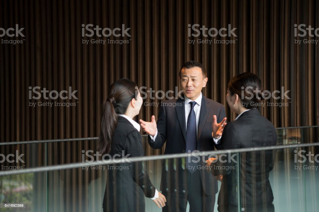 Three Japanese business colleagues talking in modern office stock photo