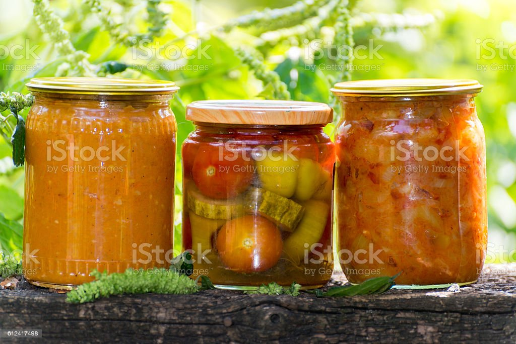 Three jars of canned vegetables outdoors stock photo
