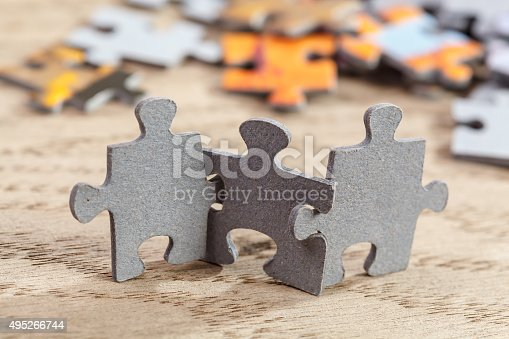 Concept of teamwork: Three jigsaw puzzle pieces on a table joint together. Shallow depth of field