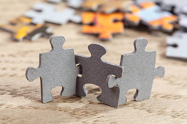 three jigsaw puzzle pieces on table - jigsaw puzzle stock photos and pictures