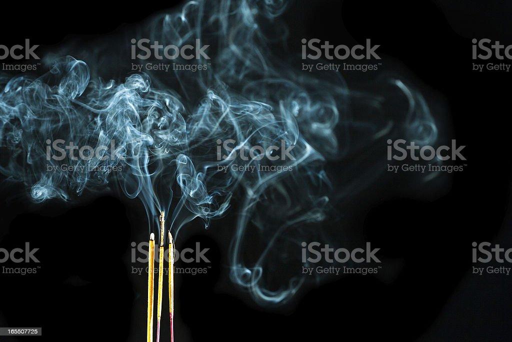 Three Joss sticks smoking on a black background stock photo