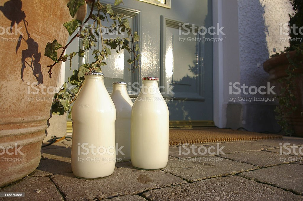 Three jugs of fresh milk sitting at the front doorstep stock photo
