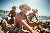 Brothers and sister are having fun building a sandcastle on a beach on a sunny summer day.\nNikon D810