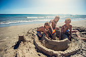 Brothers and sister are having fun building a sandcastle on a beach on a sunny summer day. Kids have put a spanish flag on top of castle.\nNikon D810