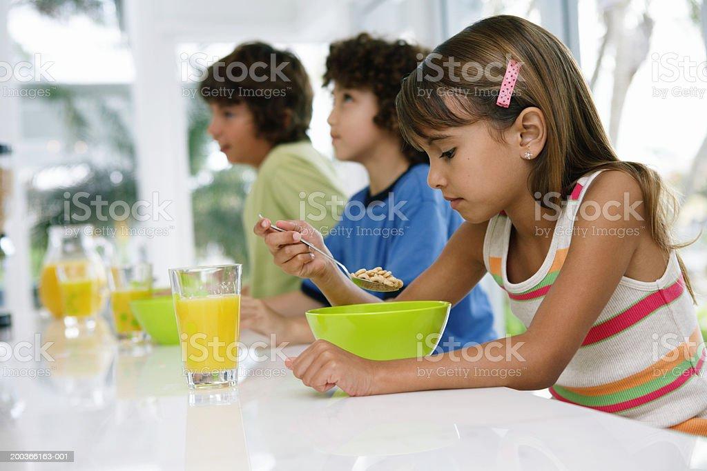 Three kids (8-10) at table, having breakfast royalty-free stock photo