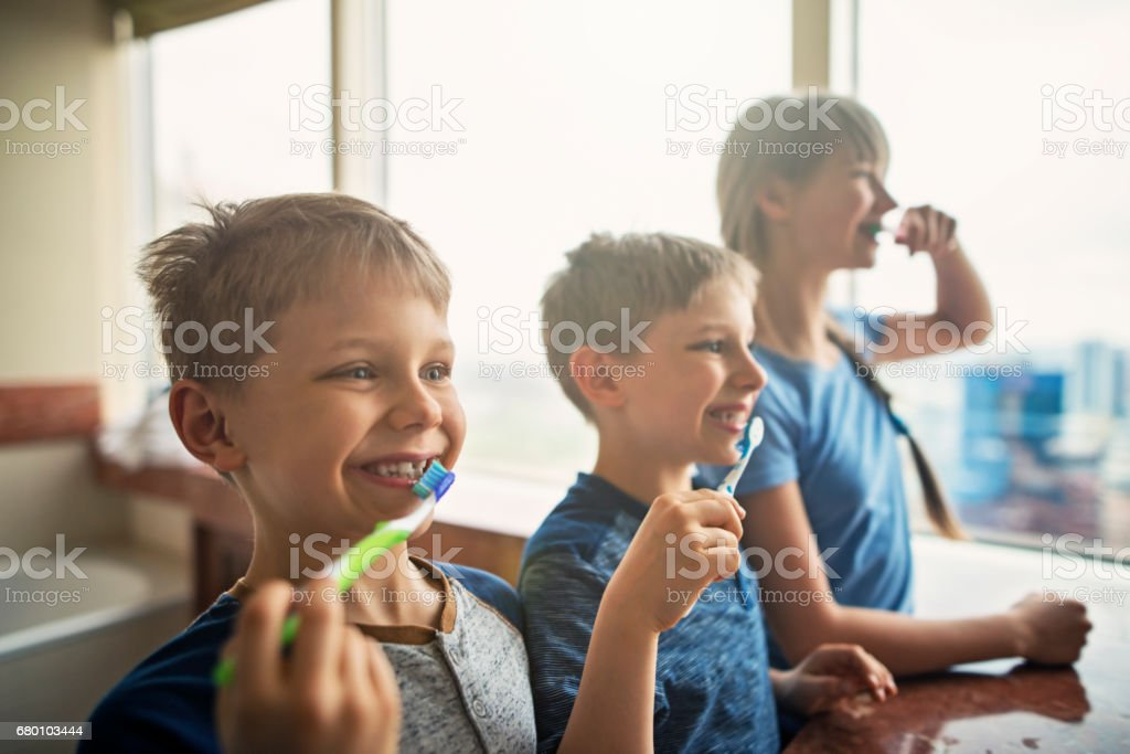 Three kids brushing teeth stock photo