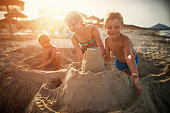 Happy kids are building sandcastle on a beach. Sunny summer evening. Majorca, Spain.\n
