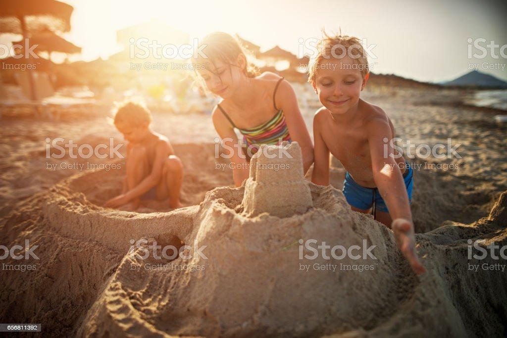 Three kids building sandcastle on beach stock photo