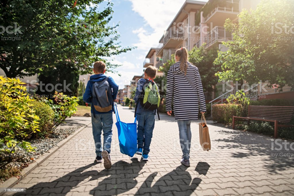Three kids carrying shopping home in resusable shopping bags - Royalty-free Backpack Stock Photo