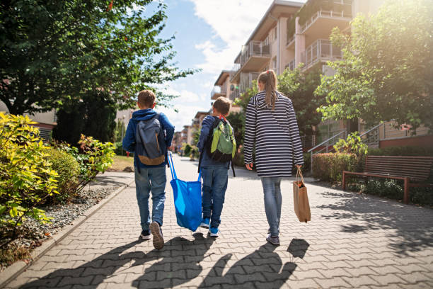 Three kids carrying shopping home in resusable shopping bags stock photo
