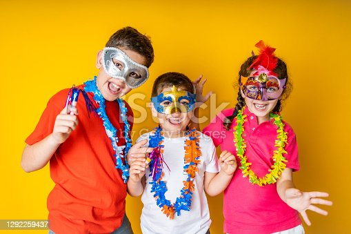istock Three kids celebrating Carnival or New Years Eve at home 1292259437