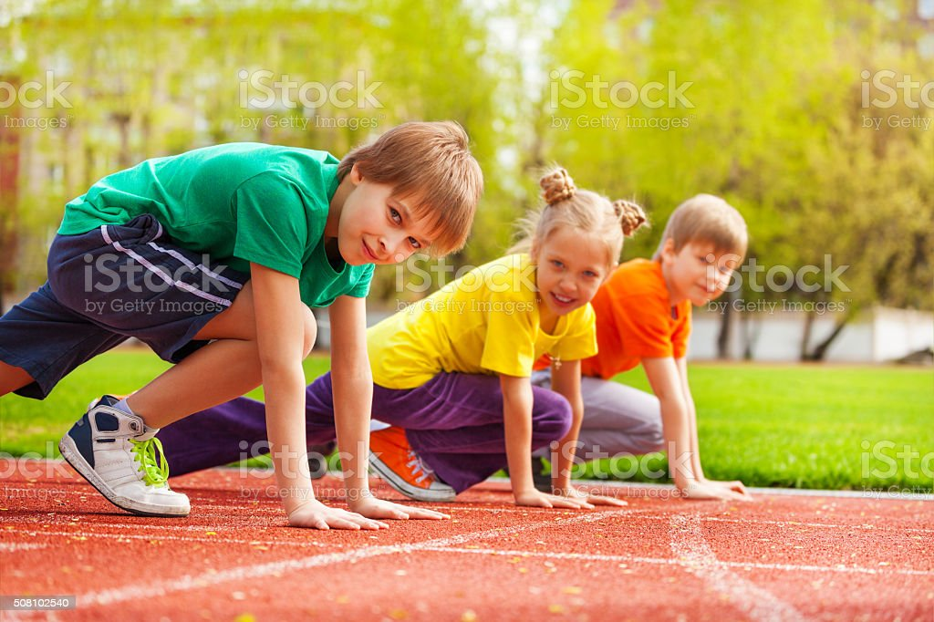 Three kids close-up in uniforms ready to run stock photo