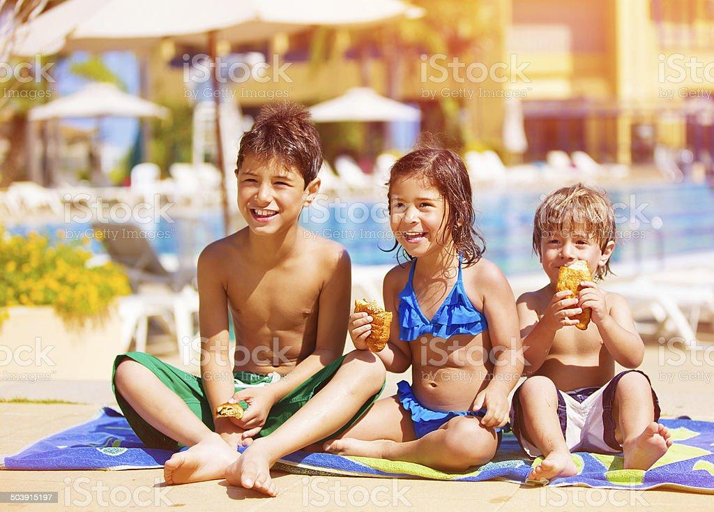 Drei Kinder essen in der Nähe des Pools – Foto