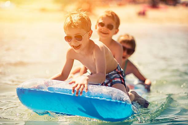 Three kids having fun in sea on air bed stock photo