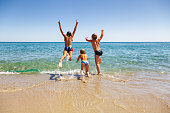 Happy children having fun on a beach running and jumping to the sea enjoying summer vacation
