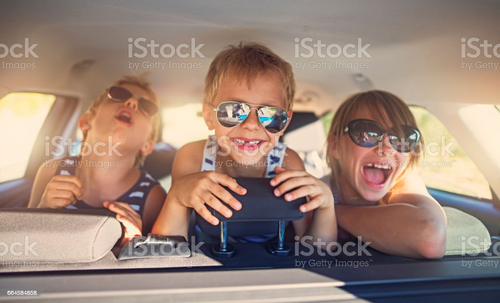 Three kids having fun on road trip stock photo