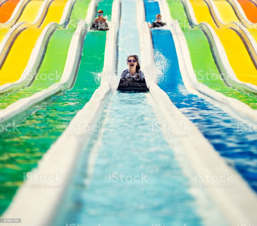 Three kids having fun sliding in a waterpark royalty-free stock photo