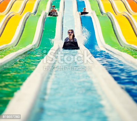 Little girl sliding on water slide, her brothers visible in the background. Sunny summer day in waterpark.