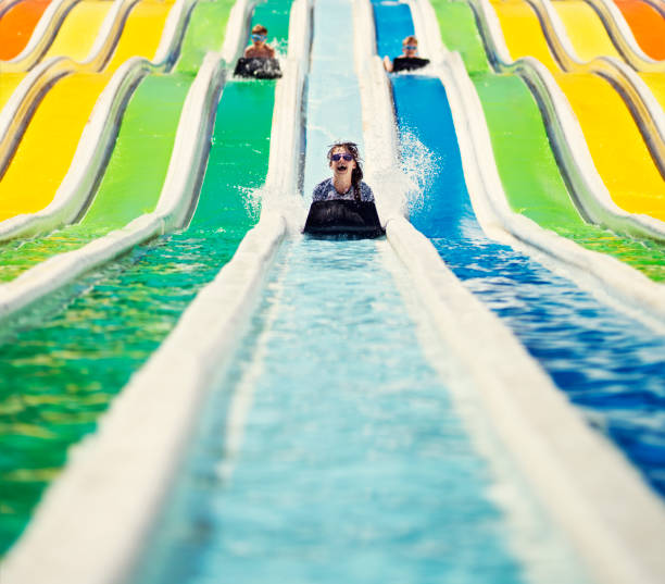 three kids having fun sliding in a waterpark - sliding stock photos and pictures