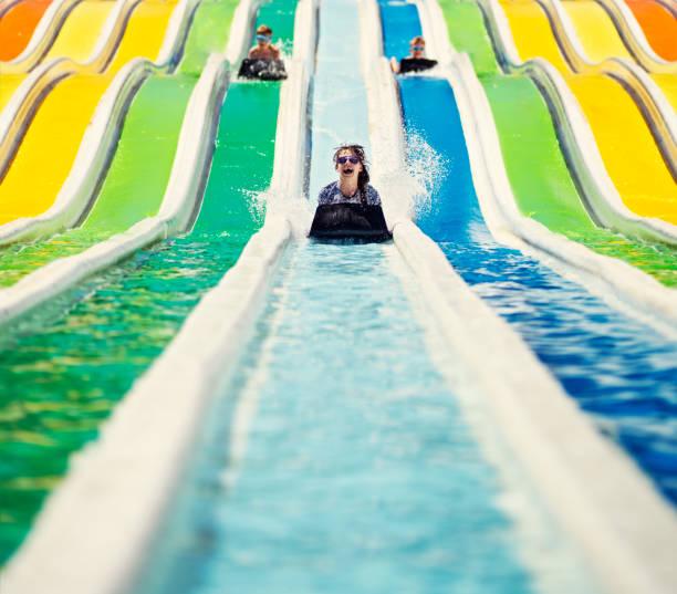 Three kids having fun sliding in a waterpark stock photo