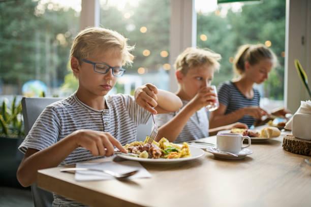 tre barn som äter måltid tillsammans - bordsskick bildbanksfoton och bilder