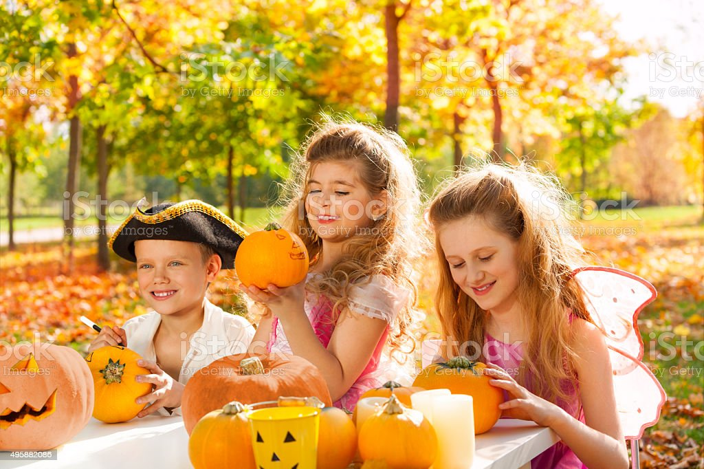 Three kids in costumes crafting Halloween pumpkins stock photo