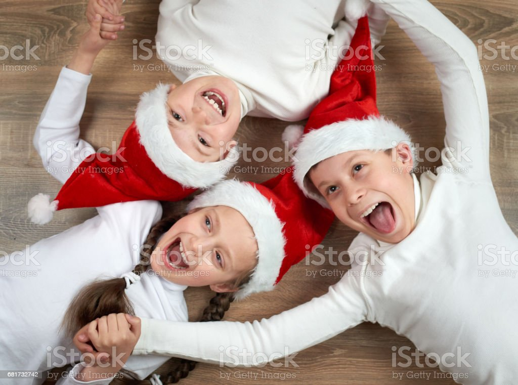 2204eb27106 Three Kids In Santa Hats Lying On Wooden Background Having Fun And ...