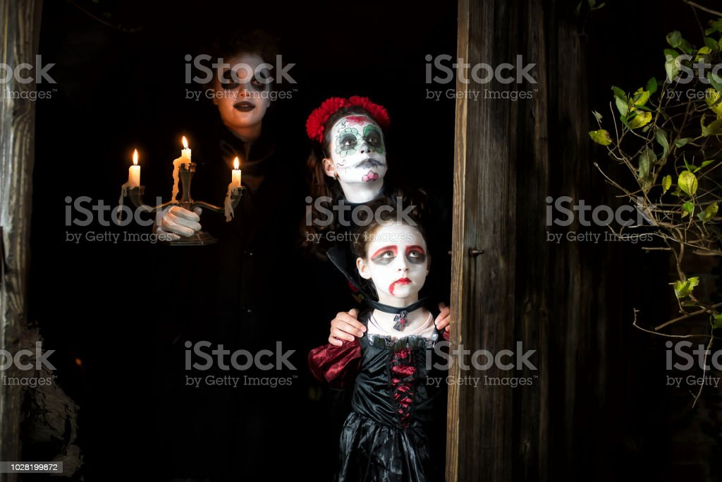 three kids in spooky halloween costumes hiding behind door of barn royalty free stock photo